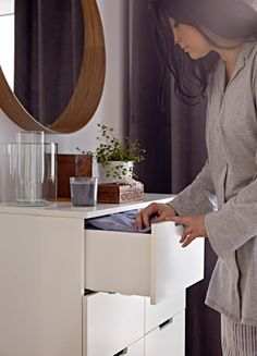 Close-up of woman getting clothes out of an IKEA chest of drawers.