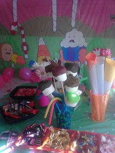 Adventure Time party Candy table with cotton candy forest backdrop in the background