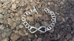 "Our Baby ""T"" Infinity Bracelet is a one of a kind gift for small children.  Infinity design is made from 14 gauge silver with 18 gauge connecting circles. Bracelet is handcrafted and 5 ½ inches in length. Lengths can be added as your child grows for FREE.  $48.00"