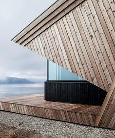 upon a challenging mountain top with views of the surrounding landscape, oslo-based architecture firm arkitektvaerelset has built a striking wooden cabin. Secluded Cabin, Wooden Cabins, Main Entrance, Natural World, Wood Paneling, Sliding Doors, Interior And Exterior, Landscape, Architecture