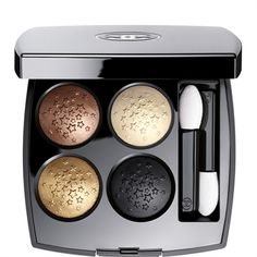 "RÊVE D'ORIENT eye shadow quad from Chanel: ""This striking eyeshadow quad creates looks that intrigue and entrance. Embossed with a precious star design, shades of glimmering beige, rich gold, luminous brown and deep black dress eyes in gilded glamour."""
