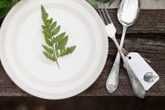 Top view of white plate with green leave and silver spoon and fork with blank label on wooden table Objects: - white plate with green leave; - fork and spoon Forks And Spoons, Silver Spoons, Snow White Cake, Wooden Tables, Rustic Table, Vintage Table, Blank Labels, Beige Background, White Plates