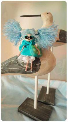 Broche o colgante en forma de muñeca con coletas de lana.