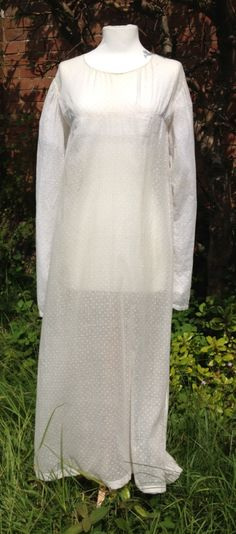 c1810 white spotted muslin gown. Very high-waisted. Over-long sleeves would be worn ruched on arm. Drawstring ties at back