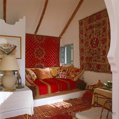 The daybed in the small whitewashed living room of the poolhouse is covered with colourful Moroccan textiles in Spain