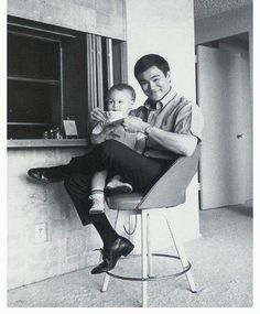 Baby Brandon Lee with father Bruce Lee.  Love that chair!