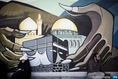IRAN, Tehran : An Iranian man and woman sit under a mural bearing the holy Kaaba of Mecca and Dome of the Rock of Jerusalem at Palestine square as they wait for the weekly friday prayers during a demonstration in Tehran on July 25, 2014 to mark Quds (Jerusalem) Day. Iranians rallied nationwide on Friday in a show of support for Palestinians and to protest against Israel as the Jewish state pursued its deadly campaign against the Gaza Strip enclave. AFP PHOTO/BEHROUZ MEHRI