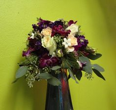 White and champagne roses combine with purple dendrobium orchids, lisianthus, raspberry and purple stock, stephanotis, waxflower, and seeded eucalyptus. A light sprinkle of glitter on the flowers provides a subtle touch of sparkleand reinforces the feeling of a winter wedding.