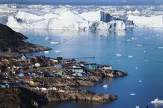 The village of Ilulissat is seen near icebergs that broke off from the Jakobshavn Glacier on July 24, 2013 in Ilulissat, Greenland. As the sea levels around the globe rise, researchers are studying the melting glaciers and the resulting long-term ramifications. The warmer temperatures that have had an effect on the glaciers in Greenland also have altered the ways in which the local populace farm, fish, hunt and even travel across land. (Photo by Joe Raedle/Getty Images) #