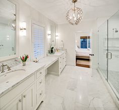 The master bath has marble detailing throughout. The countertops and flooring are both white Carrera marble. The mirrors were custom made to match the cabinetry panels. Beveled subway tiles cover the shower walls and a marble mosaic tile with a marble inlay make up the shower floor.