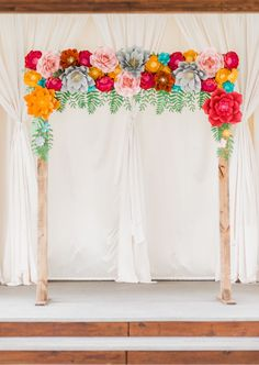 paper flower ceremony arch - photo by Laraina Hase Photography http://ruffledblog.com/fun-and-colorful-wedding-inspiration-with-paper-flowers