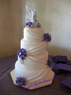 Graceful swags lifted with charming little posies by Elegant Cake Creations : http://www.elegantcakecreations.com/Pages/WeddingCakes.aspx#