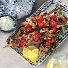 Lamb Souvlaki with Tzatziki= 1/2 cup extra-virgin olive oil 1/3 cup chopped fresh mint 1/4 cup red wine vinegar 1 tablespoon dried oregano 2 teaspoons kosher salt 1 teaspoon freshly ground black pepper 1/2 teaspoon dried crushed red pepper 8 garlic cloves, grated 1 1/2 pounds boneless leg of lamb, trimmed and cut into 36 (1/2-inch) cubes 2 lemons, cut into wedges 24 grape tomatoes (about 1 pint) Cooking spray