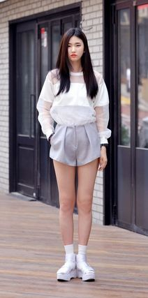 She wears a white cotton blouse with high-waisted shorts and platform sneakers. Nice look! -Lily