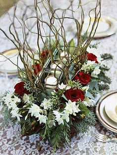 Easy to make centerpiece - with or without twigs.  The votive candles in square glass holders along with the red & white fresh flowers along the sides is elegant. I love low centerpieces to accommodate dinner conversations.