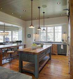The cabinets in this kitchen are pecky cypress & were custom built by John Zook.  The painted cabinets are in a distressed teal green shade with a dark brown glaze finish to create a sense of patina.