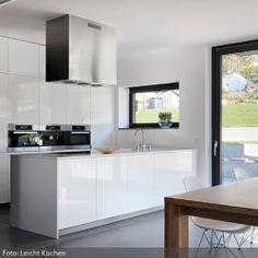 Die offene Küche in Weiß zeichnet sich durch moderne Einheitlichkeit aus. Auch die Abzugshaube fügt sich in den von rechten Winkeln dominierten Look ein. Der…