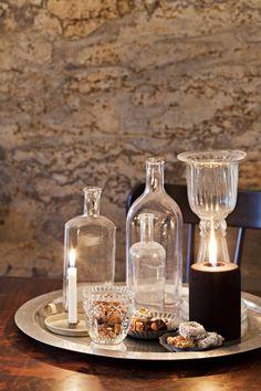 Asetelmat muuttuvat vuodenaikojen mukaan. Nyt esillä on jouluisia herkkuja ja kynttilöitä. Tarjotin on ostettu Ikeasta, lasipullot kirpputoreilta ja muut tuotteet Mosa Interiorsista.