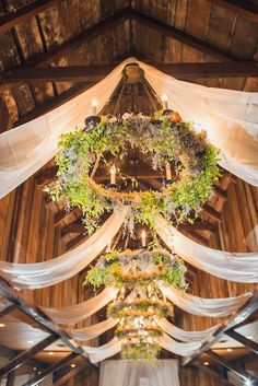 Swaged fabric and low hanging chandeliers trimmed with greenery. Source: Fab You Bliss #weddinglighting #barnwedding