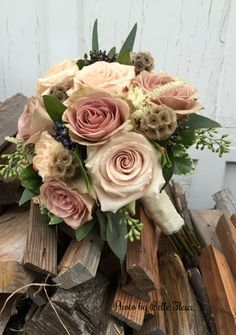 Bride's bouquet featuring Amnesia and Quicksand roses, nigella pods viburnum berries, and seeded eucalyptus. Photo by Belle Fleur.