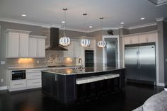 This stunning kitchen by Prodigy Homes Inc, features trendy white cabinets with granite counters and wood floors. Modern pendant lights above the dark island add a unique contemporary flair Paint Color-Functional Gray SW 7024