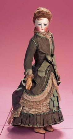 Gaultier,circa 1875. The poupee wears her original couturier gown of bronze green and aqua silk,green knit stockings,slippers,undergarments,earrings,and has elaborate and original arrangement of hair. 41 cm.