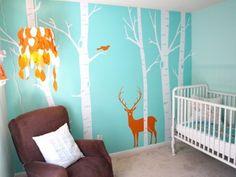 peinture chambre bébé à jolis motifs sur un fond bleu, canapé marron, lit à barreaux blanc