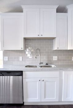 An example of gray subway tile in a white kitchen with white grout. Smoke Gray glass subway tile, white shaker cabinets, pull down faucet - gorgeous contemporary kitchen. Kitchen Cabinets Decor, Kitchen Redo, New Kitchen, Copper Kitchen, Rustic Kitchen, Kitchen Storage, Awesome Kitchen, Kitchen Organization, Condo Kitchen