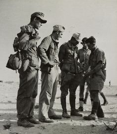 British soldier in uniform for hot climates scours German prisoners from the 90th Infantry Division of the Wehrmacht Afrika Korps captured in the area of El Alamein in North Africa.