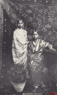 An unusual postcard view dated 1909 shows two saree-wrapped young ladies in a studio setting. No blouses can be seen because of the closely draped sarees, and other details are a little indistinct. The effect is quite atmospheric, muted and sublime. A large-scale geometric design on the seated model's saree glows silkily, while the carpet behind adds a dark richness as well. I'd believe they are sisters, but we really don't know anything.