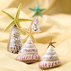 Cone-shape seashells mimic the silhouette of trees so make a tiny tree farm as a tabletop display. Pair miniature starfish with the small shells and brush the stars with a mixture of half glue and half water. Sprinkle with glitter and glue to the top of the conical shells. When dry, arrange your tiny trees in a tray of beach sand.