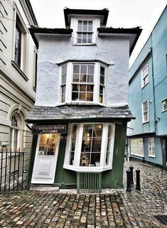 The Crooked House of Windsor, England. A quintessential English tea room.  The Crooked House of Windsor, also known as the Market Cross House, was built in 1592. It features a now-blocked secret passageway that leads to Windsor Castle and is said to have been used for trysts between King Charles II and his mistress. The house didn't start to tilt until 1718 after it was restructured with unseasoned green oak. The building now functions as a tea house for patrons who don't mind sitting at a…