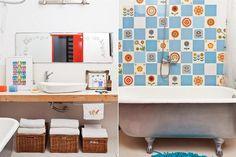 Como un patchwork pero con mosaicos, así se le dio vida a la pared donde se apoya la bañera antigua pintada de plateado en su exterior. En la zona de la bacha, se generó espacio de guardado con canastos de rattan y se sumaron detalles de colores.  /Archivo LIVING