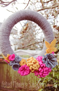 DIY: felt flowers five ways  Could make a great outdoor party decoration; cover a foam donut in satin fabric and attach artificial flowers and then hang from a tree.  Maybe even add some string lights.