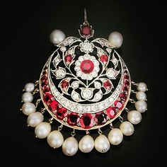 A ceremonial mang tika or a head ornament for Indian women from the 19th century. This statement piece is laden with diamonds and rubies in different sizes in a Mughal floral pattern that rests above a crescent shaped motif and is adorned with lovely natural pearls. The mang tika is a classic jewel that belongs to every bridal's bijouterie which essentially comprises of 16 traditional ornaments (Solah shringaar). It sits prettily on the forehead as its worn on the hair line and on the…