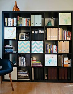 What a great IKEA hack... This is how a bookshelf should be done! Just take canvases to fit the cubes, cover them in whatever art you want, and attach them using screw eyes and cup hooks to hide whatever clutter is on that shelf