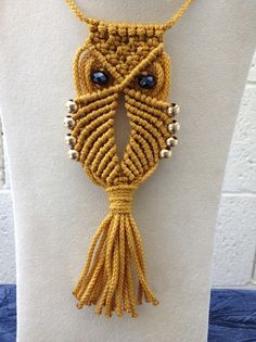 Owl pendant measures 6 x 2 1/4 inches. Crafted in gold cord with gold beads.