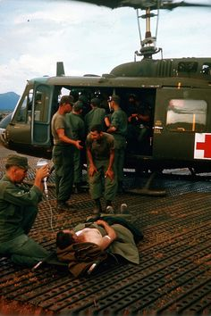 Wounded soldier receiving transfusion outside helicopter, Vietnam. Huey. Bell UH-1. Thank you Vietnam vets for your service!