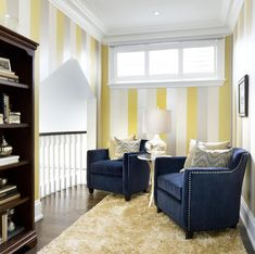 A small sitting room near the small balcony overlooking the family room has light taupe, yellow and white stripes on the walls, a fluffy pale yellow rug covering the hardwood floors, and navy armchairs with metallic tack accents. Gray from the walls is reflected in the accent pillows on the chairs. A short window high on the wall provides extra light during the day.