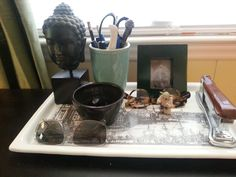 Buddha contemplates a catch-all tray on the library desk.