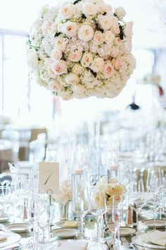 Cylindrical vessels were topped with round arrangements composed of vanilla hydrangea blossoms, as well as cream and blush roses. #flowerarrangement #centerpiece Photography: David & Tammy Molnar