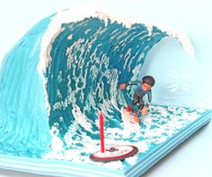 A chocolate mud cake layered with ganache, disguised as a wave. I got my inspiration from a cake made by Anne Heap. The customer supplied me with photographs so I could add personal details on the model. Such as design on surf board and wet suit....