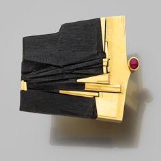 Othmar ZSCHALER / ring gold, ebony and ruby. Grande bague abstraite Le plateau trapézoïdal est composé d'une sculpture moderniste sur ébène bordée d'or jaune poli et ponctué d'un cabochon de rubis. Poids brut : 33,2 gr. Dimensions du plateau : 3,8 x 3,8 cm