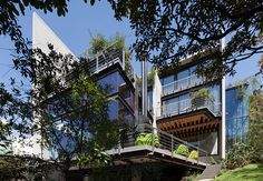 House in the Forest by Grupo Arquitectura is located in a suburb of Mexico City and features an outdoor elevated glass walkway offering views to the lush green courtyards below...