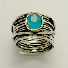 Imagine life in peace ~~~~~~~~~~~~~~ The blue opal is lying safe and protected in a silver nest. (R1505). © 2011 Artisanimpact Inc. All rights reserved.  Construction & Dimensions: ~~~~~~~~~~~~~~~~~~~~~~~ Sterling silver, opal. Approximate width: 16mm (0.49in).  The ring with the gold bezel is listed separately. We can make any size, including quarter sizes. For this wider band, we suggest adding .25 to you current thin ring size. Please just indicate the requested size in the order.  About…
