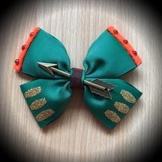 Merida Disney Princess Ispired Brave Hair Bow  Dark Green Grosgrain Ribbon Decorated with Gold Glitter, Orange Felt, Orange Rhinestones, Brown Strap and Arrow Centrepiece.  Mounted on an alligator clip.  I can do custom bows, just let me know if youd like something specific.  Price is for single bow.