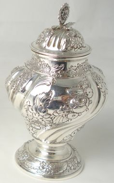 A late Victorian silver tea caddy & cover  by C.S Harris, London 1899   Of inverted pear shape, with spiral fluting and embossed with floral garlands, the pull off cover with cast flower finial, and a brandy pan, stand and burner with wooden handle, by Hamilton & Inches, Edinburgh 1904, height of caddy 14cm, weight 11.2oz gross.