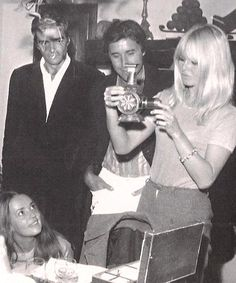 1965: Brigitte gets her presents during her 31st birthday party, with her co-star Jeanne Moreau and her boyfriend Bob Zagury by her side