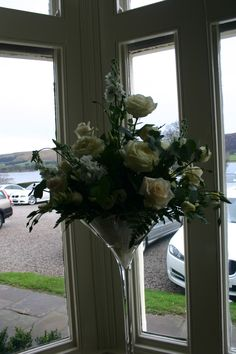 Ivory roses, stocks, lizianthus and mixed foliage in tall martini vase