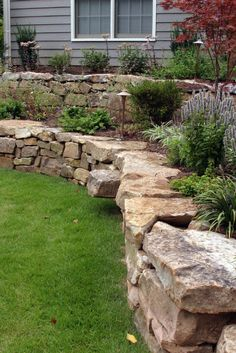 50 Backyard Retaining Wall Ideas and Terraced Gardens (Photos) : A hand-laid retaining wall made out of natural stone. Two terraces are filled with low maintenance landscaping. The terraces smooth out angle between the much higher house and the lawn.
